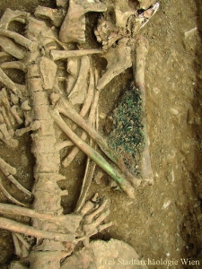 """Neuer Schottenfriedhof: Totenkronen aus gezwirbeltem Filigrandraht und anderen Schmuckteilen waren vom 16. bis zum 19. Jahrhundert bei der Bestattung von Kindern und ledig Verstorbenen beliebte Beigaben. Sie symbolisierten die im Tode vollzogene Hochzeit mit Christus. Saß die """"Brautkrone"""" nicht auf dem Kopf, konnte sie – wie in diesem Grab – in die Arme oder Hände gelegt werden."""